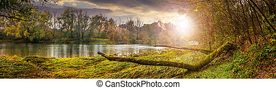 mountain river with fallen tree on the shore at sunset -...