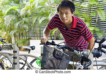 asia man take bike in bicyle park