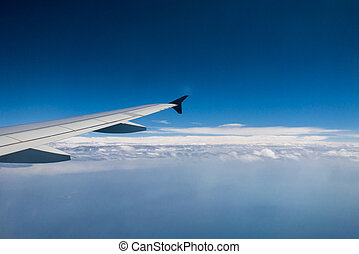 Airplane flying over the clouds - Aircraft wing flying over...