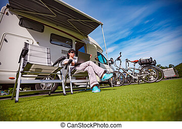 Woman sitting on a chair near the camper and looking at a...