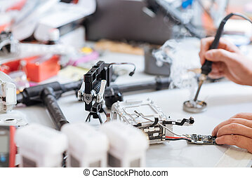 Close up of mans hands soldering drone mechanism - Creating...