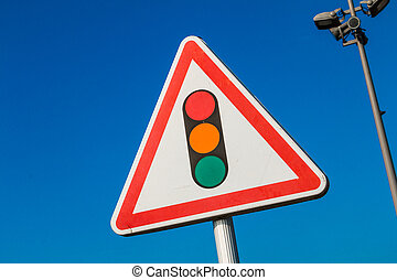 warning sign with a picture of a traffic signal on blue sky