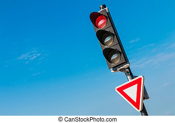 red traffic light with yield sign on blue sky