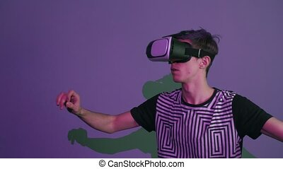 Young man with purple bangs using vr glasses doing gestures...