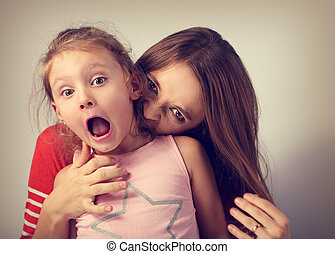 Angry emotional young mother wanting to bite her naughty capricious daughter