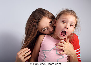 Angry emotional young mother wanting to bite her naughty capricious daughter with screaming nervous frightened face and open mouth on blue background. Humor concept portrait