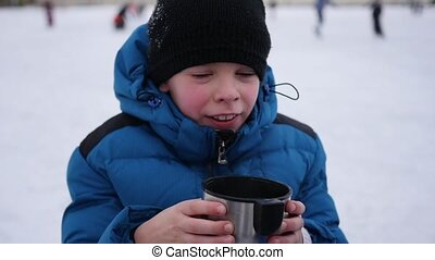 the kid is drinking hot tea from a mug in the winter outdoor. ice rink.