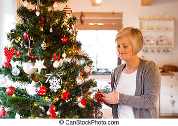 Senior woman at home decorating Christmas tree. - Beautiful...
