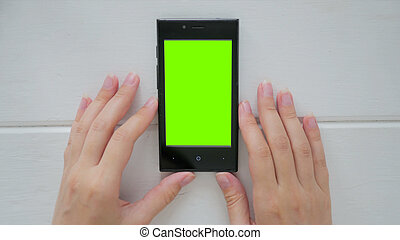 Woman looking at smartphone with green screen - Woman...