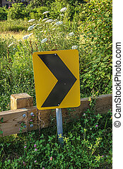 Turn way road sign on roadside in front of green plants and...