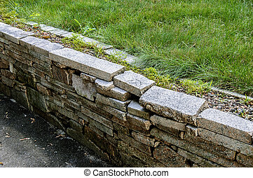 Granite wall made of bricks and fresh lawn grass shot with place for text on a sunny day