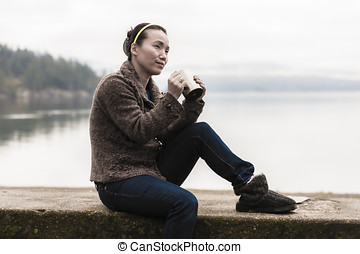 Woman with coffee by the lake.