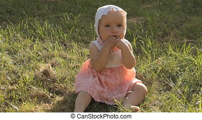 A baby girl fiddling with her dirty fingers in the mouth using both hands.