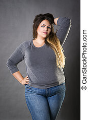 Young beautiful plus size model in blue jeans, xxl woman on...