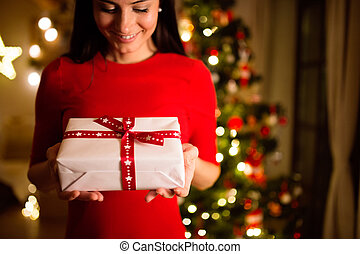 Young woman in front of Christmas tree giving present