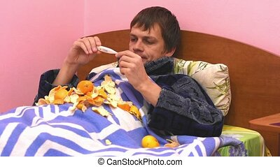A sick man lying in bed, measuring the temperature and eats...