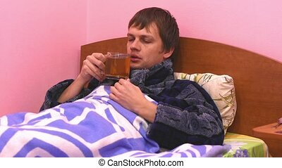A sick man lying in bed and drink hot tea