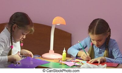Two children doing crafts, one cuts with scissors colored...