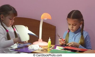Two children cut with scissors pieces of colored paper, making crafts