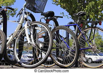 Bikes and cars at a park and ride - Close up view of...