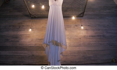 Wedding white dress hanging on iron lattice inside dark...