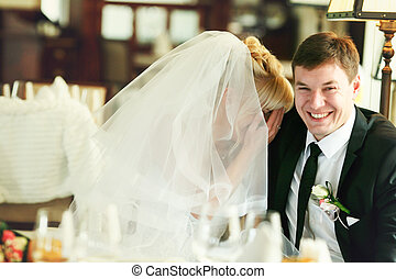 Bride hides her face behind her palms sitting with a groom
