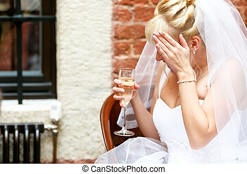 Bride hides her face behind a palm sitting with a glass of champagne