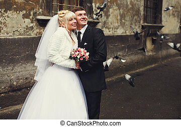 A wedding couple watches flying pigeons