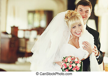 Bride laugh holding a white shawl on her shoulders