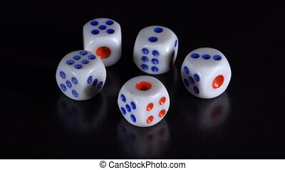 Dice rotate on a black table - White dice rotate on a black...