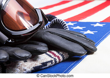 Close up shot of winter sport goggles with gloves and hat over US flag