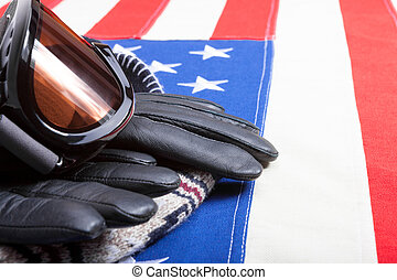 Winter sport goggles with gloves and a hat over US flag