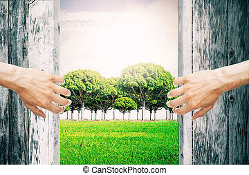 Nature concept - Hands opening abstract aged wooden doors,...