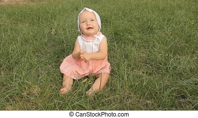 A baby girls grimacing, clapping hands and showing a branch...