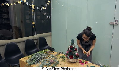 Brunette florist makes floral arrangement on table inside...
