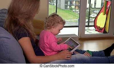 woman with child watch family photographs on tablet computer screen