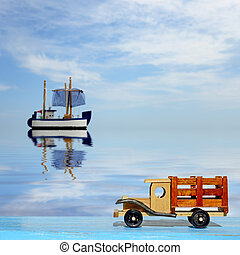 Toy truck car on a blue wooden surface and toy sailboat at...