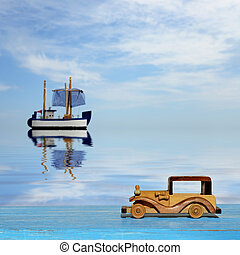 Toy car on a blue wooden surface and toy sailboat at sea