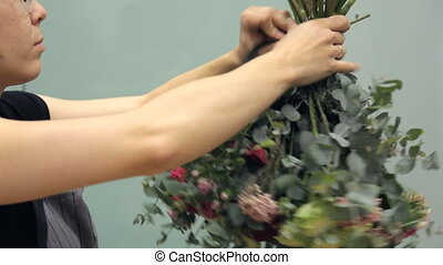 Flower arranger wraps a round bouquet around with a dark...