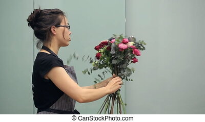 Florist with all concentration collects flowers in bouquet.