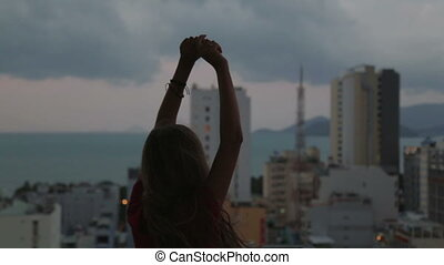 woman on the roof of a skyscraper raises his hands