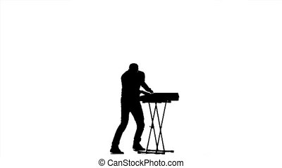 Man playing on a synthesizer. Jumps to the music. Silhouette...