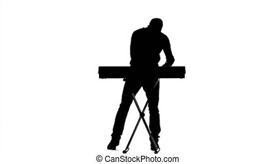 Emotionally plays on electronic piano young man. Silhouette....