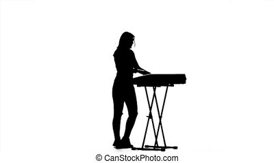 Girl standing at the piano dancing and clapping. Silhouette....