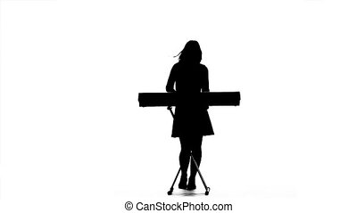 Silhouette of a girl playing the synthesizer. Slow motion -...