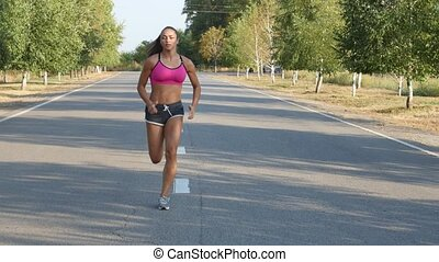 Beautiful sportswoman running on a country road. Training...