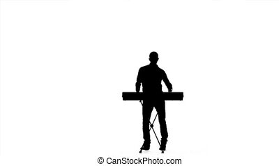 Young man playing on an electronic piano. Silhouette. Slow motion