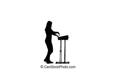 Silhouette of the girl in the half turn plays the piano,...