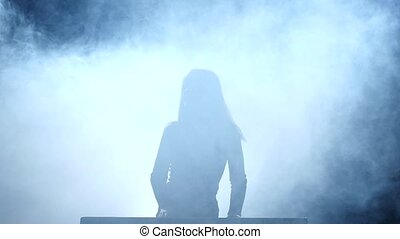 Girl on the smoky stage playing the piano. Slow motion -...
