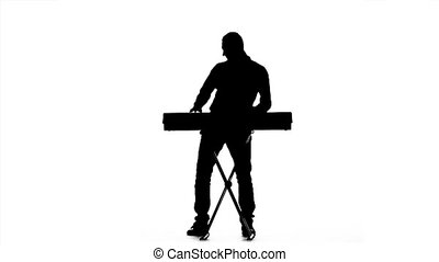 Young man having fun playing the piano. Silhouette. Slow motion